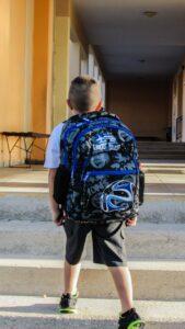 Lille dreng med skoletaske på ryggen på vej i skole
